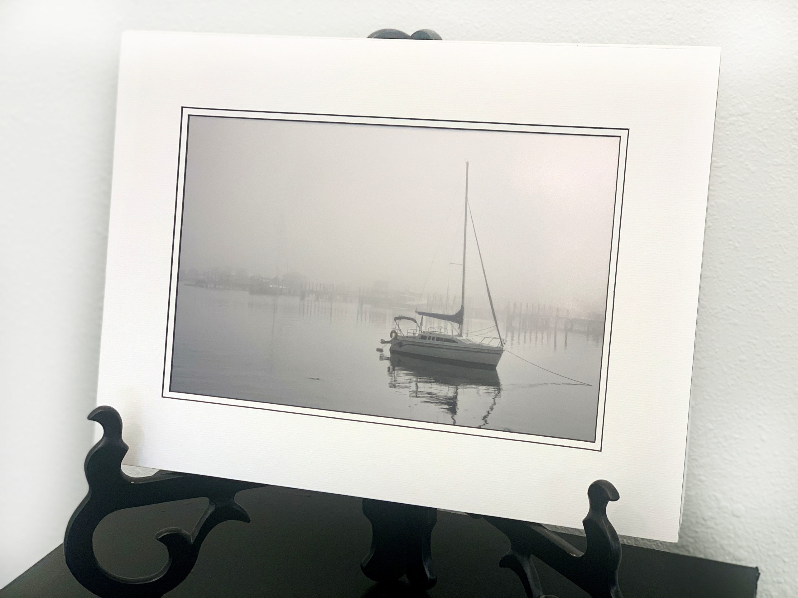 black and white sail boat on misty lake
